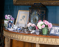 A giltwood demi-lune table displays a collection of personal objects and garden flowers
