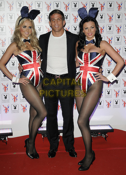 Alex Reid & Playboy Bunnies .At the opening of the Playboy Club, Old Park Lane, Mayfair, London, England, UK, June 4th 2011..Full length black suit white t-shirt Hermes belt union jack costume ears outfit bunny .CAP/CAN.©Can Nguyen/Capital Pictures.