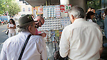 Men waiting to purchase lottery tickets from a street booth, Seville, Spain