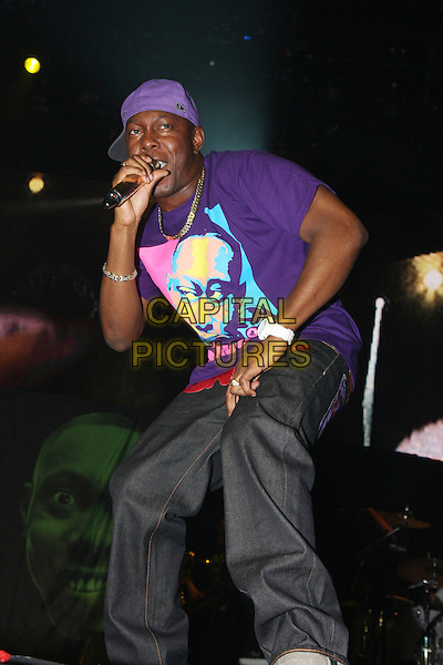 DIZZEE RASCAL (Dylan Kwabena Mills).Performing live at the 02 Arena, London, England..March 7th, 2010.stage concert gig performance music full length jeans denim purple t-shirt singing baseball cap hat .CAP/MAR.© Martin Harris/Capital Pictures.