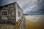 The old wharf building at Okarito has weathered many West Coast storms and stands defiant as more inclement  weather rolls in from the Tasman Sea...This New Zealand Fine Art Landscape Print, available in four sizes on either archival Hahnemuhle Fine Art Pearl paper or canvas, is printed using Epson K3 Ultrachrome inks and comes with a lifetime guarantee against fading..All prints are signed and numbered on the lower margin and come with my 100% money back guarantee on the purchase price, should you not be  completely happy with the quality of the delivered print or canvas.