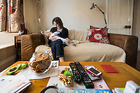 A young woman breastfeeding her baby at home while sitting on  sofa in her living room.<br /> <br /> 15/05/2012<br /> Hampshire, England, UK