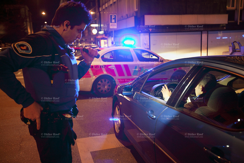 Switzerland. Geneva. A police officer with a flashlight in his left hand and his right hand on his Glock gun control the identity of a group of men. The men come from the neighboring french area and want to party in the Paquis neighborhood, known for its nightlife and Red-light district. They will all be left free after the control. The policeman is wearing a ballistic vest, bulletproof vest or bullet-resistant vest which is an item of personal armor that helps absorb the impact from knives, firearm-fired projectiles and shrapnel from explosions, and is worn on the torso. Soft vests are made from many layers of woven or laminated fibers and can be capable of protecting the wearer from small-caliber handgun and shotgun projectiles. 24.03.12 © 2012 Didier Ruef..