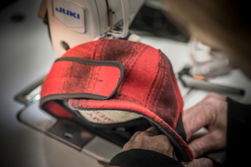 A step in the Stormy Kromer manufacturing process attaching the ear flap and string at the Ironwood, Michigan production facility.