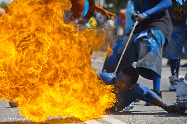 Traditional mas  - Blue devils breathing fire on the ground playing mas in the street