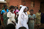 MPHANDULA, MALAWI - AUGUST 19: Suzana Nabanda, age 16, walks with her sister and relatives after a marriage ceremony on August 19, 2006 in Mphandula village, about 30 miles outside Lilongwe, Malawi. She just got married to a farmer a few hours earlier. Mphandula is a poor village in Malawi, without electricity or clean water. Nobody owns a car or a mobile phone. Most people live on farming. About 7000 people live in the village and the chief estimates that there are about five-hundred orphans. Many have been affected by HIV/Aids and many of the children are orphaned. A foundation started by Madonna has decided to build an orphan center in the village through Consol Homes, a Malawi based organization. Raising Malawi is investing about 3 million dollars in the project and Madonna is scheduled to visit the village in October 2006. Malawi is a small landlocked country in Southern Africa without any natural resources. Many people are affected by the Aids epidemic. Malawi is one of the poorest countries in the world and has about 1 million orphaned children. (Photo by Per-Anders Pettersson)