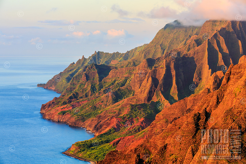 The low light of the sunset adds its glow to the red and green of the Na Pali coastline, as seen from the Nu'alolo Trail, Kaua'i.