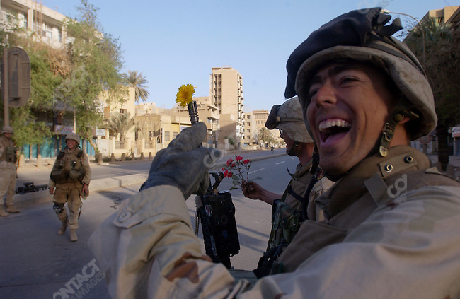 For the attention of foreign pix-A US Marine who had just been given a flower by an Iraqi woman jockingly put it down the barrel of his M16 as  he laughed with his colleagues on the morning after US forces had taken control of central Baghdad. April 10, 2003