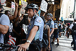 A police officer delights in blocking demonstrators on State Street at Lake under the El marching in support of a Citizens Police Accountability Council to provide civilian oversight of the Chicago Police Department in Chicago, Illinois on July 11, 2016.  The demonstration attracted a larger crowd on the heels of last week's racially charged police shootings captured on video of Alton Sterling in Baton Rouge, Louisiana and Philando Castile in the St. Paul suburb of Falcon Heights, Minnesota which was followed by a mass shooting of five police officers by Afghan War veteran Micah Johnson who supported radical and violent black nationalist ideology.