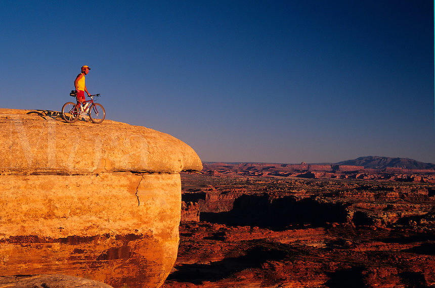 Mountain biker enjoying late afternoon view from atop  White Crack Rock in Canyonlands National Park, Moab, Uta