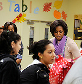 First Lady Michelle Obama and daughter Malia Obama, far left, pack and give bags of food to area residents at Martha's Table on Wednesday, November 24, 2010, in Washington, DC.  .Credit: Leslie E. Kossoff - Pool via CNP
