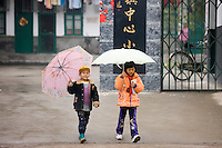 Young girls leave the playground of a primary school in Fuli. China has a one child policy to limit population.
