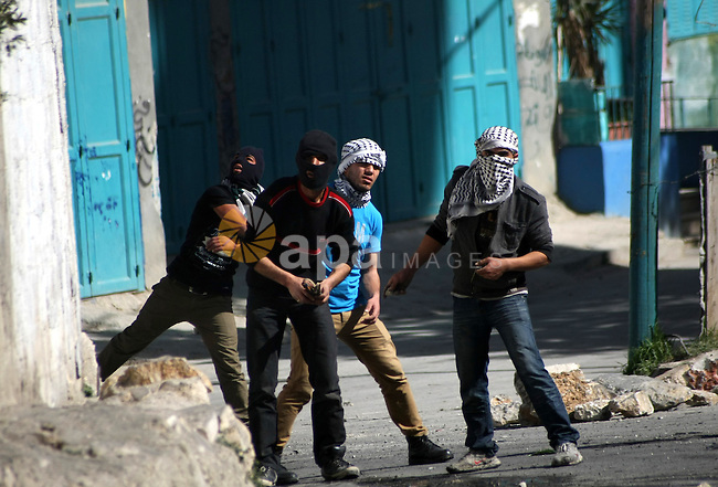 Palestinian protesters throw stones at Israeli security forces during clashes in al-Aroob refugee camp near the West Bank town of Hebron on February 26, 2013. Increased protests in the West Bank after the killing of a Palestinian Prisoner Arafat Jaradat, 30, whose death in an Israeli jail on 23 February sparked riots across the Israeli-occupied West Bank. Palestinians claim he died of torture. Israel says the initial autopsy could not determine the cause of death and further tests were needed. Photo by Mamoun Wazwaz