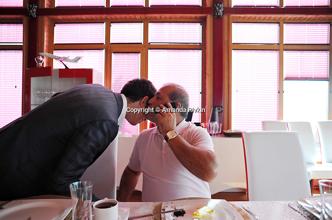 Ibrahim Ibrahimov, an Azerbaijani oligarch and billionaire, kisses his eldest son Huseyn, 18, on the cheek whilst talking on his cell phone at the breakfast table in one of several houses on his Caspian seaside property he used to inhabit with his family in the Garadagh region just southwest of Baku, Azerbaijan on July 18, 2012.  Ibrahimov is the developer behind the Khazar Islands artificial islands project; in his private life, he enjoys building a home for his family, moving in, and then quickly tires of the property before building a new home on an adjacent lot on his seaside lands.