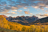 Uncompahgre National Forest, Colorado: Cliffs of the Cimarron stand above fall colored hillside in evening light; San Juan Mountains