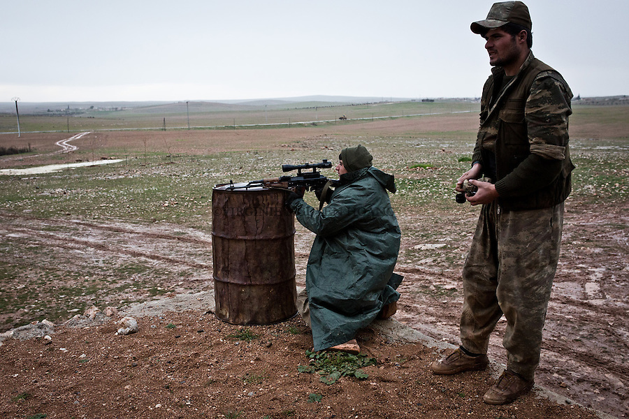 SYRIA: A YPG fighter tests his weapon at a rear base of the village of Shalabiya near the town of Tal Abyad.<br />