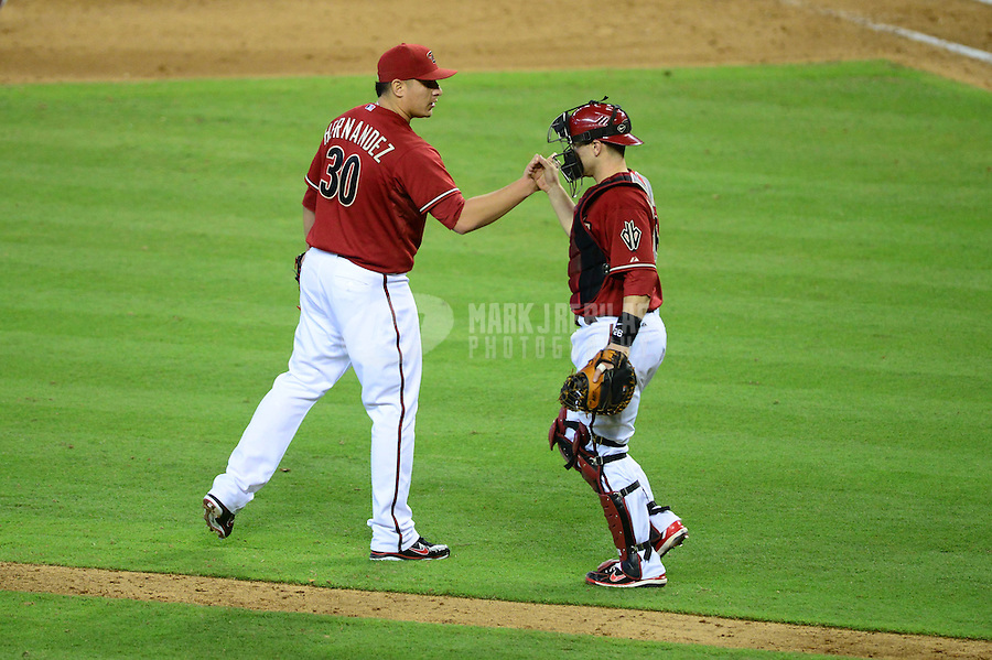 Jun. 20, 2012; Phoenix, AZ, USA; Arizona Diamondbacks pitcher David Hernandez (left) celebrates with catcher Miguel Montero following the game against the Seattle Mariners at Chase Field.  The Diamondbacks defeated the Mariners 14-10. Mandatory Credit: Mark J. Rebilas-