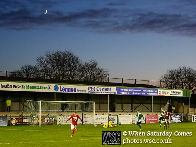 Zach Hemming of Blyth Spartans lets a shot slip from Lee Ndlovu under his body for another Brackley goal, as the crescent Moon sets behind Croft Park. Blyth Spartans v Brackley Town, 30112019. Croft Park, National League North. Photo by Paul Thompson.