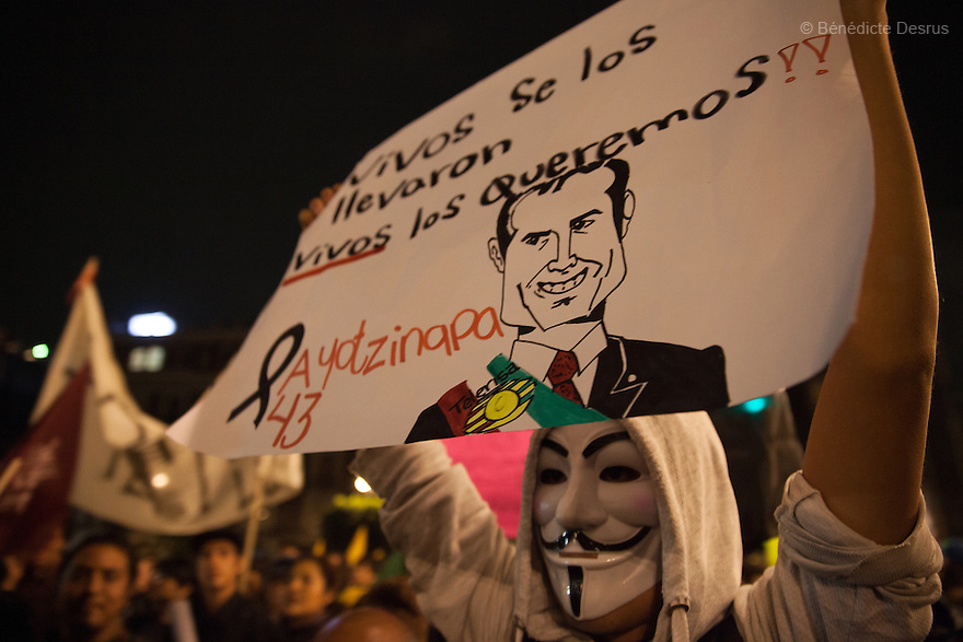 "A demonstrator wears a guy fawkes mask while holding a sign reading ""Vivos se los llevaron, Vivos los queremos"" (they were taken alive, we want them back alive) during a massive march in support of the 43 missing Ayotzinapa's students, on a day normally reserved for the celebration of Mexico's 1910-17 Revolution, in Mexico City, Mexico on November 20, 2014. Parents of the 43 missing students still do not believe the official line that the young men are all dead. Criticism of the government has intensified in Mexico and the country has been convulsed by protests. Many are demanding justice and that the search for the 43 missing students continue until there is concrete evidence to the contrary. Mexico officially lists more than 20 thousand people as having gone missing since the start of the country's drug war in 2006, and the search for the missing students has turned up other, unrelated mass graves. (Photo by Bénédicte Desrus)"