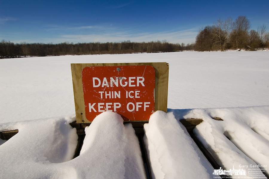 A sign warning of thin ice on a park lake is covered with snow.