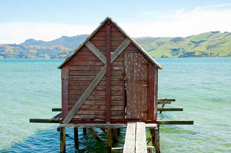 Old red boat shed over the water on the Otago Peninsula, near Dunedin, Otago, South Island, New Zealand - stock photo, canvas, fine art print