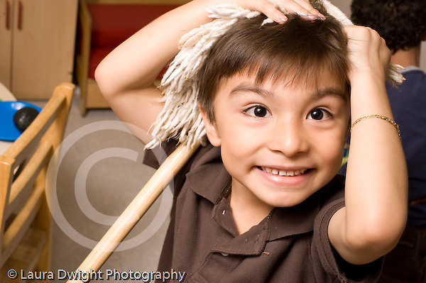 Preschool ages 3-5 boy playful portrait with toy mop on his head horizontal