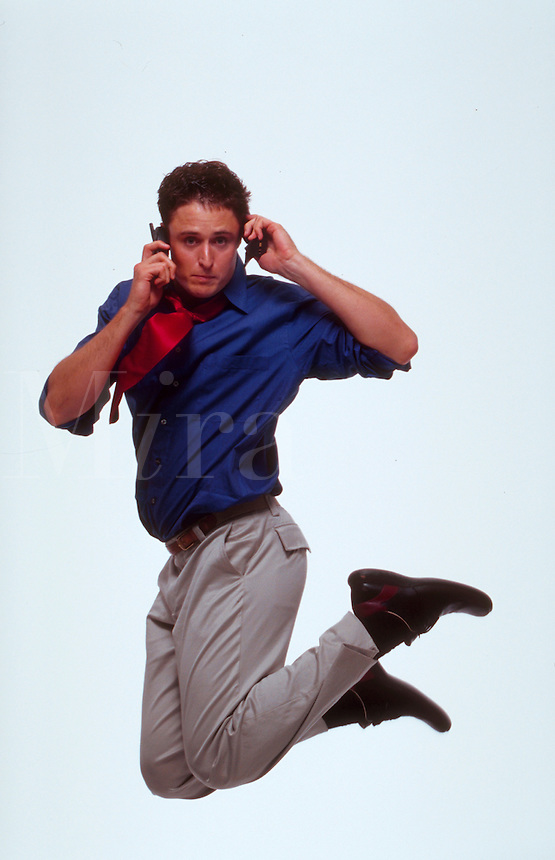 A stressed, young professional man represents The Cellular Age as he jumps with one phone to each ear.
