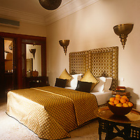A guest bedroom decorated in neutral and gold with a double bed with a patterned cover.