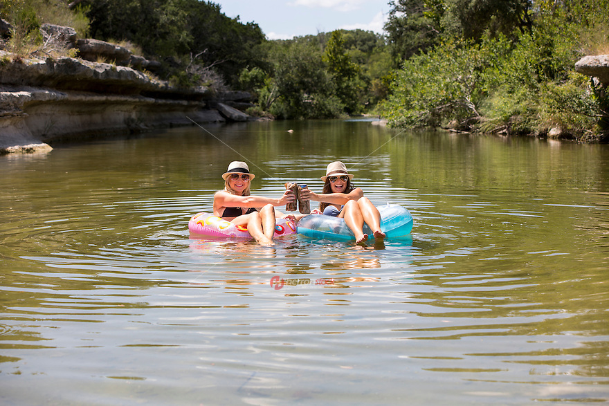 Two attractive females beat the summer heat by drinking a cold beer and relaxing in the cool waters of Bull Creek Greenbelt swimming hole in west Austin, Texas.