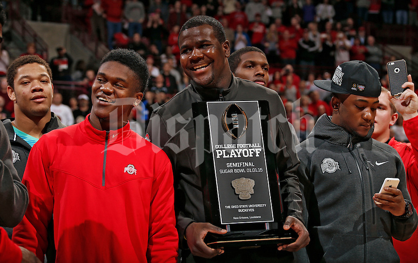 Ohio State Buckeyes quarterback Cardale Jones (12) holds a College Football Playoff semifinal trophy during a timeout of the basketball game against Illinois Fighting Illini during the 1st half of their NCAA basketball game at Value City Arena in Columbus, Ohio on January 3, 2014.  (Dispatch photo by Kyle Robertson)
