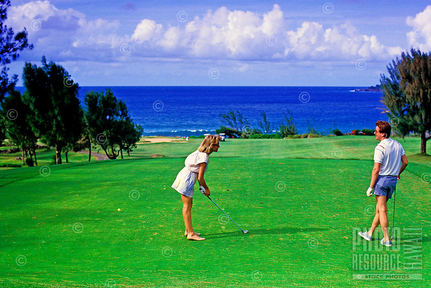 A couple enjoy the beautiful scenery at the lush Kapalua golf course on the island of Maui.