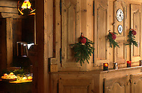 The traditional built-in wooden cupboard in the panelled dining room is decorated for Christmas