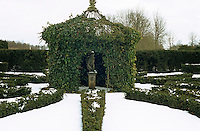 A statue is sheltered within an ivy-covered pergola in the centre of the garden