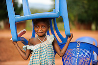 ANGOLA Kwanza Sul, village Kassombo, children on way to school, each child must bring his own plastic chair as the schools in poor condition due to the civil war / ANGOLA Kwanza Sul, Dorf Kassombo, Kinder mit Plastikstuehlen auf dem Weg zur Schule durch Felder des Dorfes, da die Schulen durch den Buergerkrieg zerstoert und ohne Inventar sind, muss jedes Kind seinen Plastik Stuhl mitbringen, Maedchen Rosaria 8 Jahre