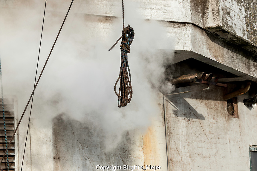 Detail from outside a grain silo, where steam are being let out from the Silo with a tight rope hanging in the foreground.