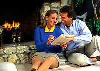 A smiling young couple sit before a cozy fire and have fun doing a crossword puzzle.