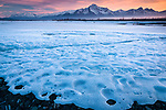 Ice sheet along Matanuska River. Sunset sky and Chugach Mountains in the background. Palmer, Southcentral Alaska, Winter.