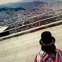 An Aymara woman, wearing the traditional bowler hat, stands on the edge of the hill in El Alto and looks down to the valley of La Paz, Bolivia, 9 February 2014.