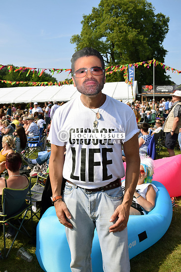 Man wearing George Michael mask at Let's Rock, 1980s retro festival in Earlham Park, Norwich May 2018