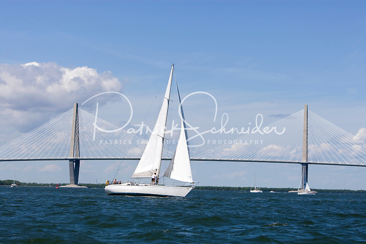 A sailboat cruises past the Cooper River Bridge in the Charleston Harbor in Charleston, SC.