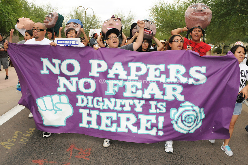 "Phoenix, Arizona (July 28, 2012) - About three hundred people marched to protest the second anniversary of the approval of some provisions of the SB 1070 immigration law. The march, called ""No Papers, No Fear"" was organized by immigrant rights groups who say the law discriminates people of brown skin. In this photograph, protesters and undocumented immigrants (from left) Miguel Guerra, Isela Meraz, Leticia Ramirez, and Natally Cruz, hold a banner as the ""No Papers No Fear"" march begins in Phoenix. All four protesters were arrested for civil disobedience acts on July 24 for blocking a major intersection in Downtown Phoenix. Photo by Eduardo Barraza © 2012"