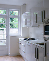 A kitchen designed in a pleasingly spare style has a refreshing all white colour scheme accentuating the light flooding in from curtainless windows