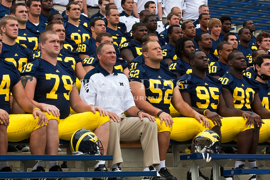 Michigan head coach Rich Rodriguez, center, sit for a team photo with his players at the annual NCAA college football media day, Sunday, Aug. 22, 2010, in Ann Arbor, Mich. (AP Photo/Tony Ding)