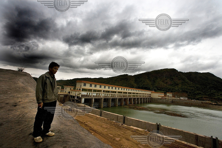 Li Zhiguang standing on a retaining wall built on what was once his land in Paitou Village. Land around the village was expropriated by the local government to make way for a new power station planned by the Fuyuan Industrial Group (seen to the back right).....