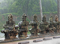 Heavy Monsoon rain over the stone faces at the entrance bridge and gate near Bayon Temple. Cambodia