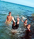 HONDURAS, Roatan, group of kids playing in water, Flowers Bay