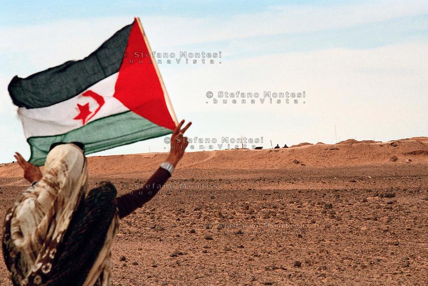 "Sahara Occidentale 15 Gennaio 2010.Una ragazza saharawi sventola la bandiera saharawi davanti al muro marocchino.Il muro marocchino o muro del Sahara Occidentale è un insieme di otto muri difensivi con una lunghezza superiore a 2.720 km costruito dal Marocco nel Sahara Occidentale. È una zona militare con bunker, fossati e campi minati, edificato con l'obiettivo di proteggere il territorio occupato dal Marocco dalle incursioni del Fronte Polisario..A girl from Western Sahara, Saharawi flag flying in front of the Moroccan Wall.The Berm of Western Sahara (also known as the Moroccan Wall) is an approximately 2,700 km-long defensive structure, mostly a sand wall (or ""berm""), running through Western Sahara and the southeastern portion of Morocco. It acts as a separation barrier between the Moroccan-controlled areas and the Polisario-controlled section of the territory that lies along its eastern and southern border."