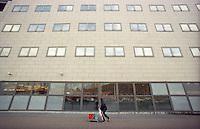 milano, quartiere bicocca, periferia nord. un addetto alle pulizie davanti a un edificio per uffici --- milan, bicocca district, north periphery. a cleaning man in front of an office building
