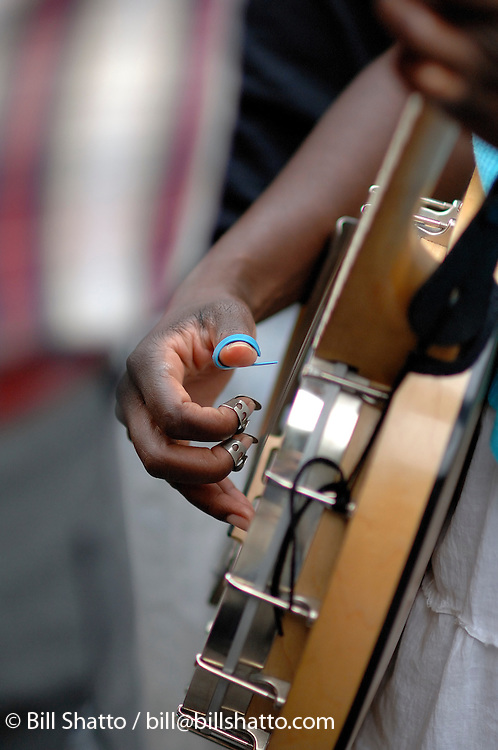 Closeup of a woman's hand playing a banjo.