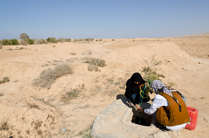 Rafallah Abdullah and his daughter Iness pull water from a nearly empty well in the desert outside of Marsah Matrouh, Egypt.